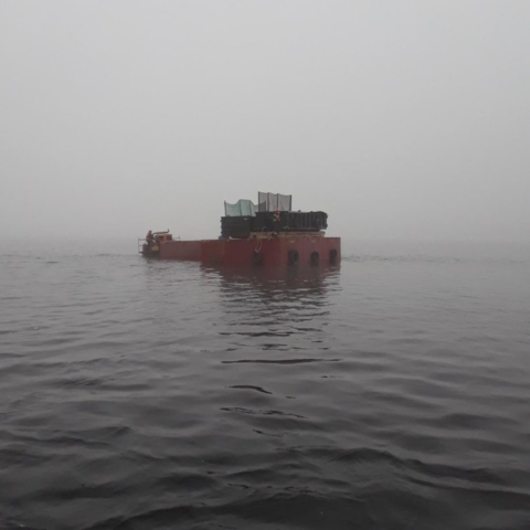 Small barge delivering containment containers to large barges