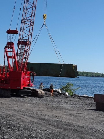 Girder being unloaded from barge