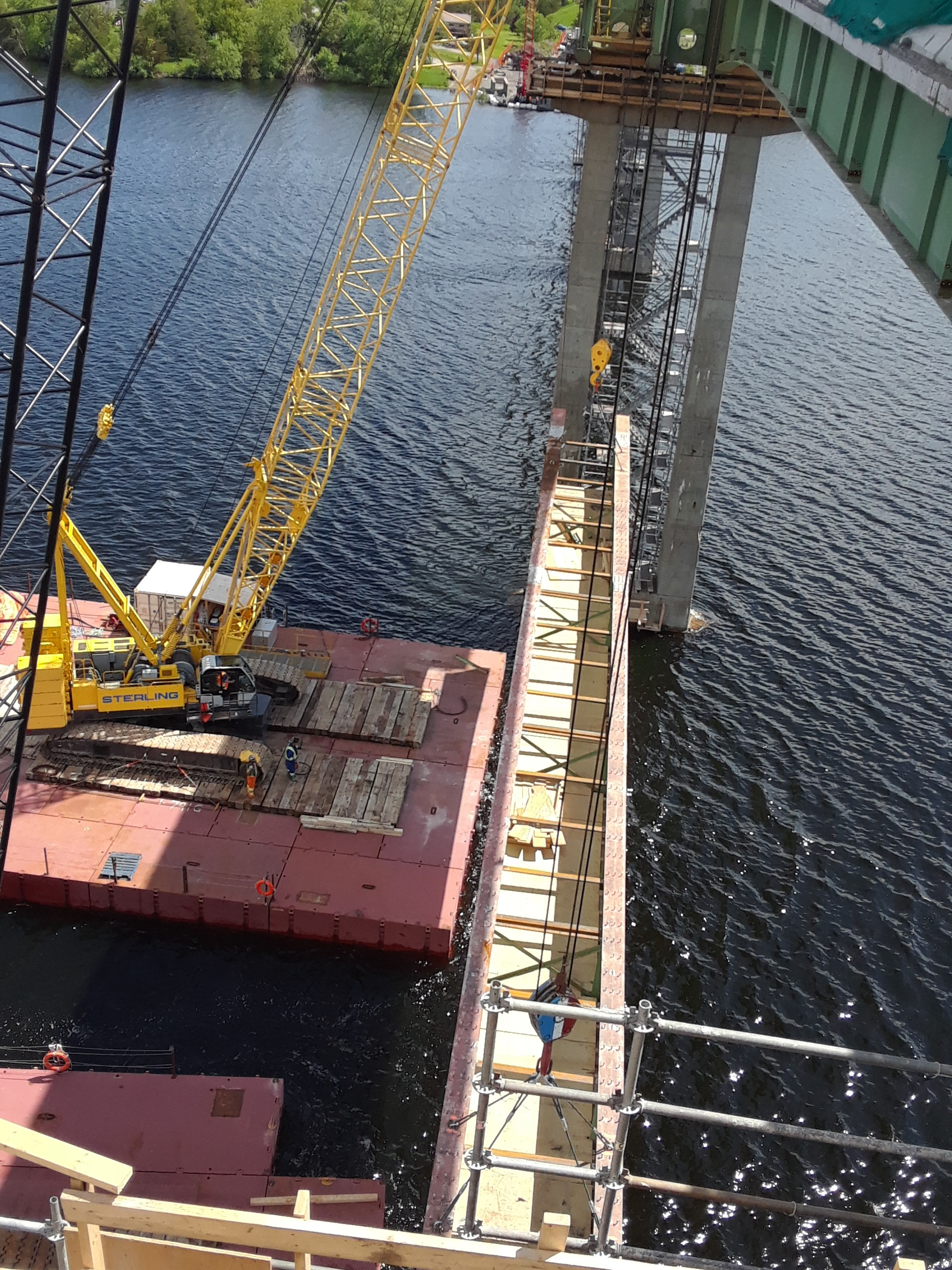 Large section of removed girder being lowered to the barges