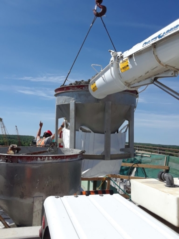 Concrete hopper filled and ready for removal by crane