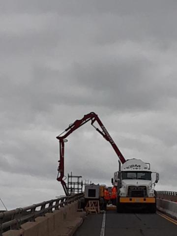Concrete pump truck pouring concrete for pier refacing