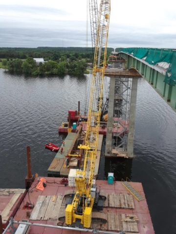 Three barges being used to prepare for girder placement