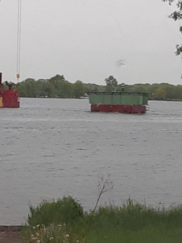 Removed piece of girder being transported to shore
