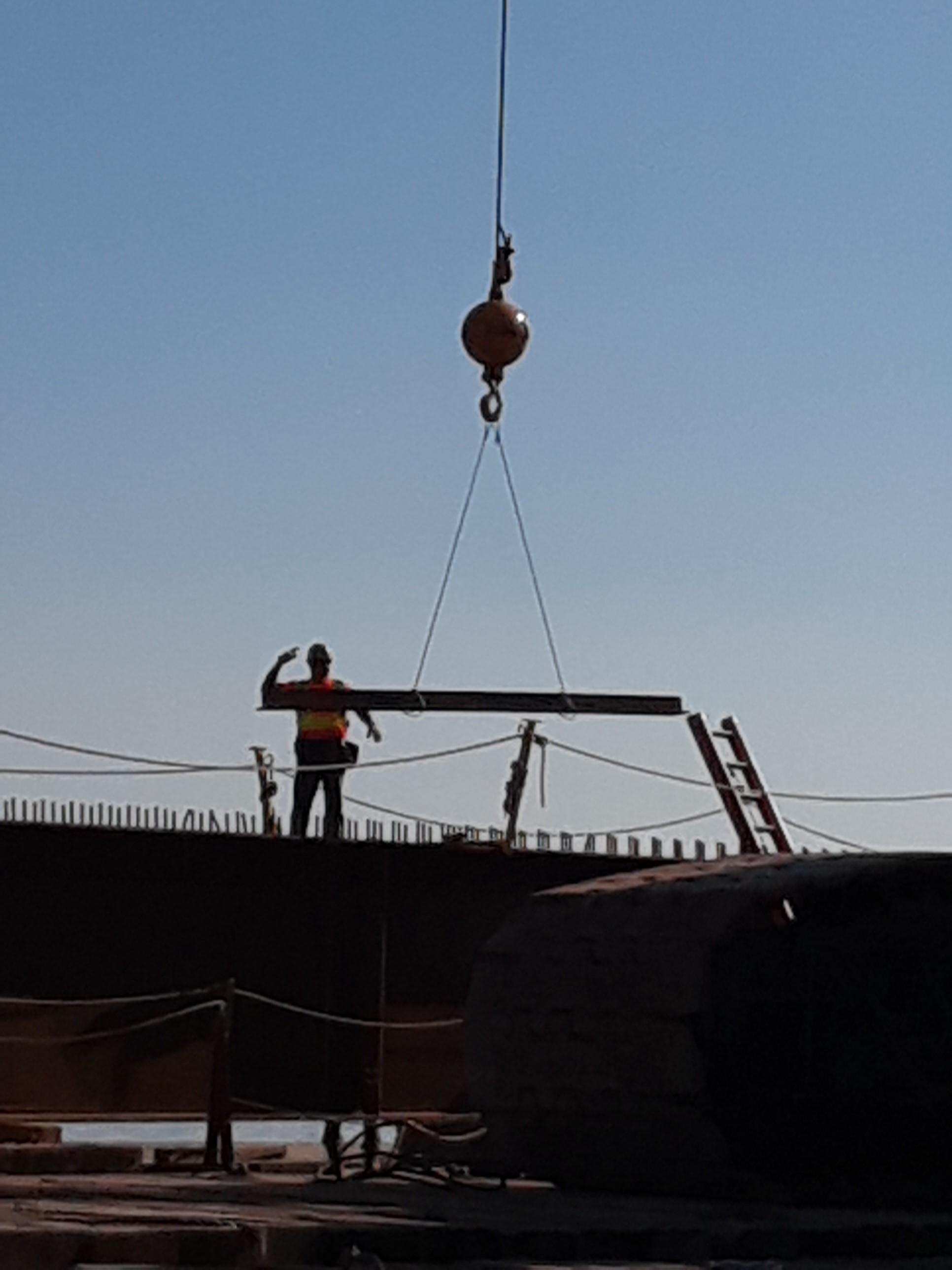Crane picking up brace for girder installation