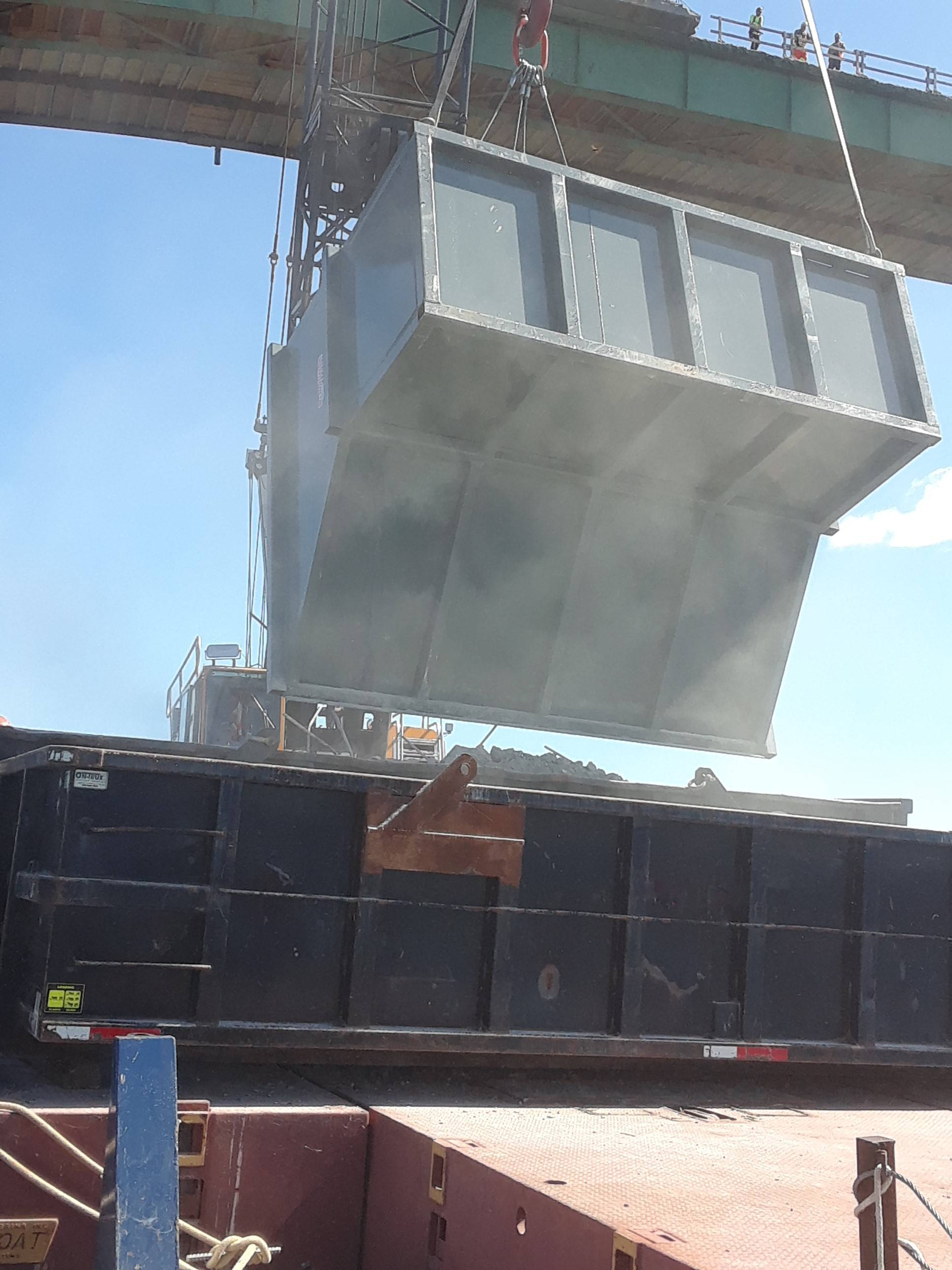 Barrier wall ruble being dumped into bins on the barge for removal