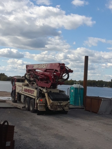 Concrete pump truck being offloaded from the barge