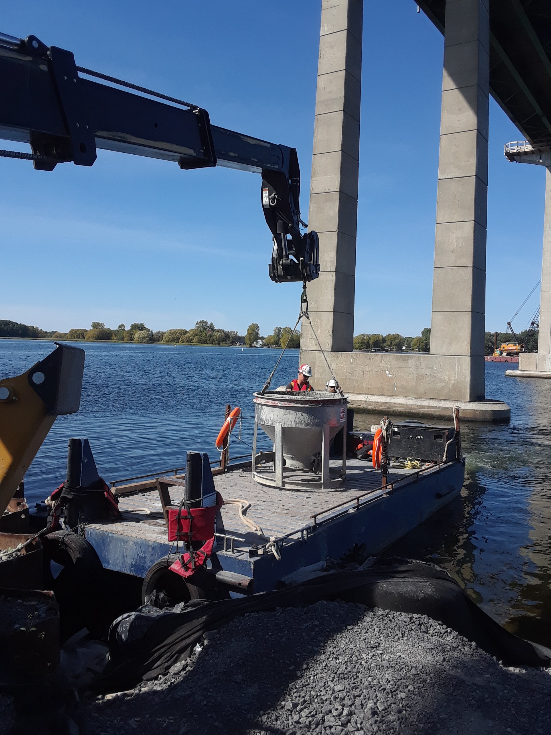 Full concrete bucket being loaded to be transported to the barge for placement