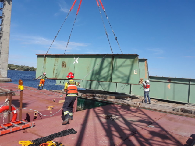 Second piece of removed girder being guided into place on the barge