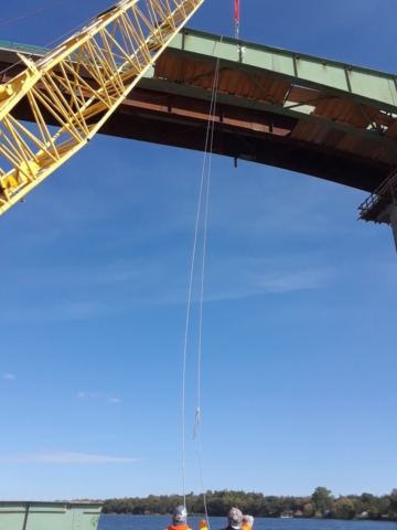 Guide ropes attached to help the third piece of girder to the barge