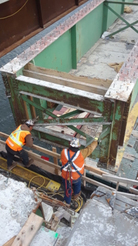 Girder being lowered, view from beside the pier cap