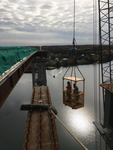 Man cage being raised from the barge to complete tasks for the new girders