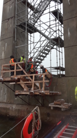 Iron workers heading up the scaffolding for the girder lift