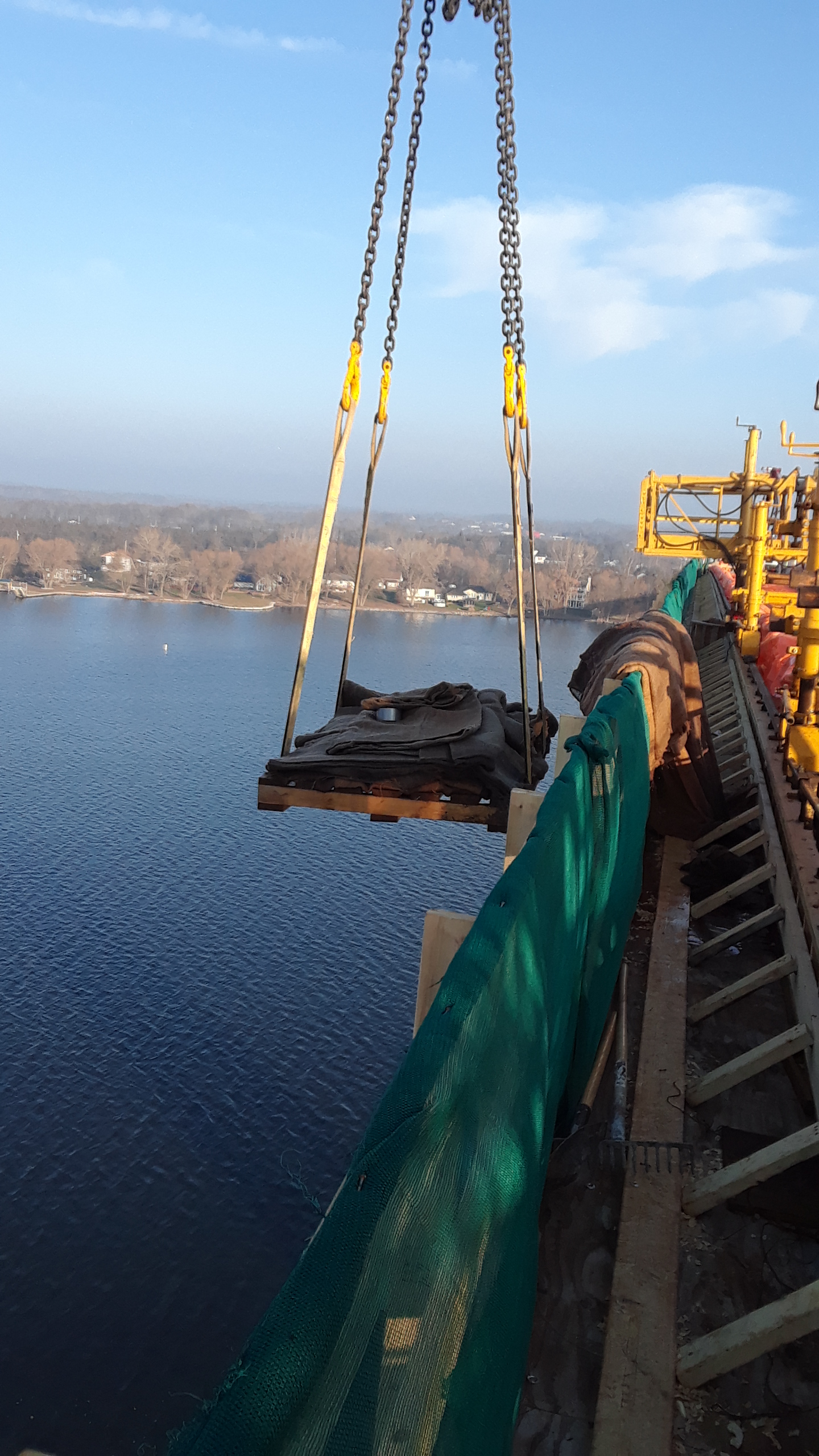 Burlap curing material being lifted from the barge
