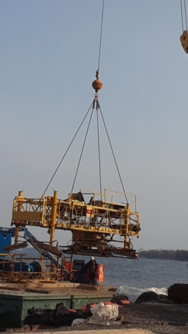 Concrete finisher being removed from the barge