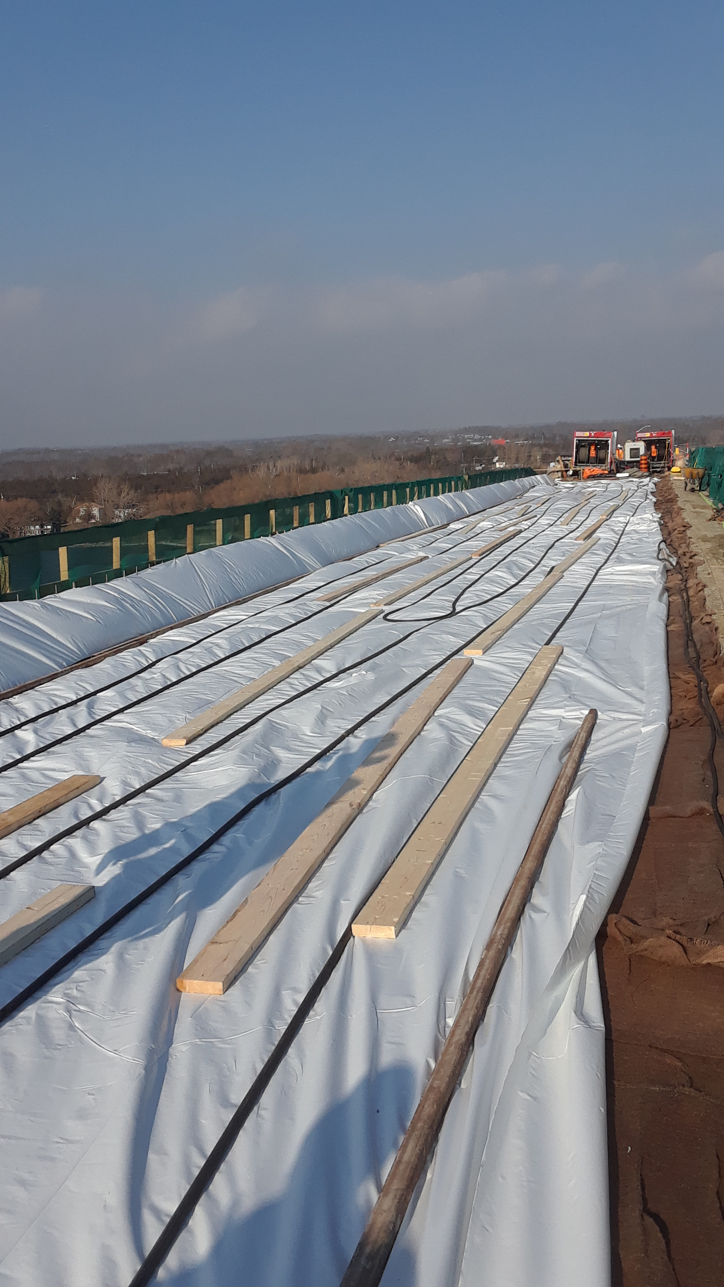 Newly placed deck covered by curing material and tarping, being heated by ground heaters