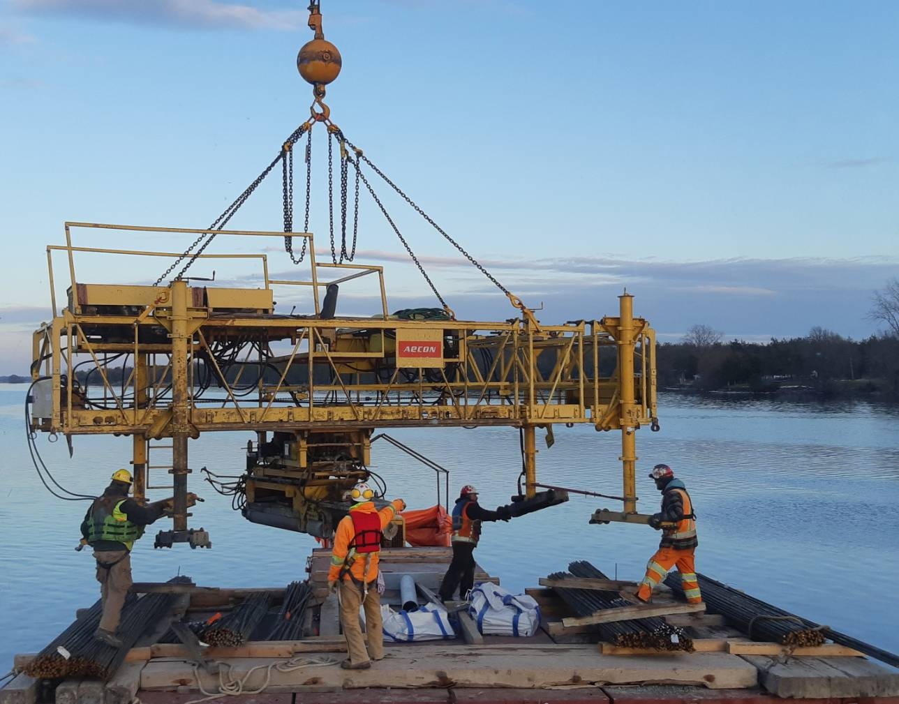 Concrete finisher being prepared to be lifted from the barge o the deck