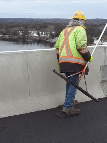 Tampering the fresh asphalt at the barrier wall
