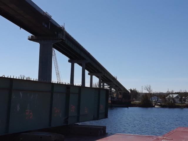 First section of removed girder being brought to shore by the barge