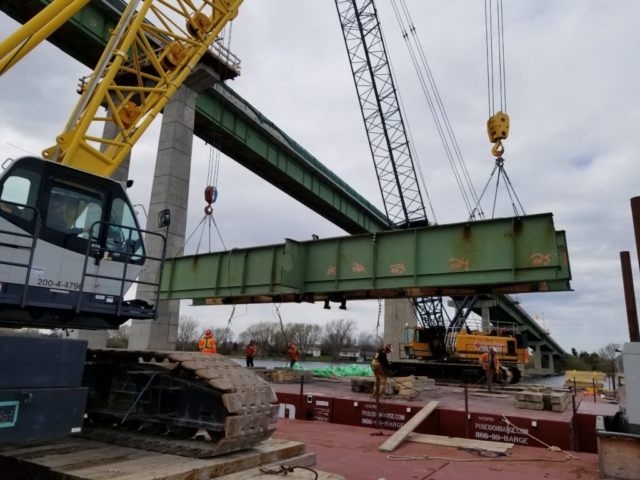 Final section of girder being lowered onto the barge