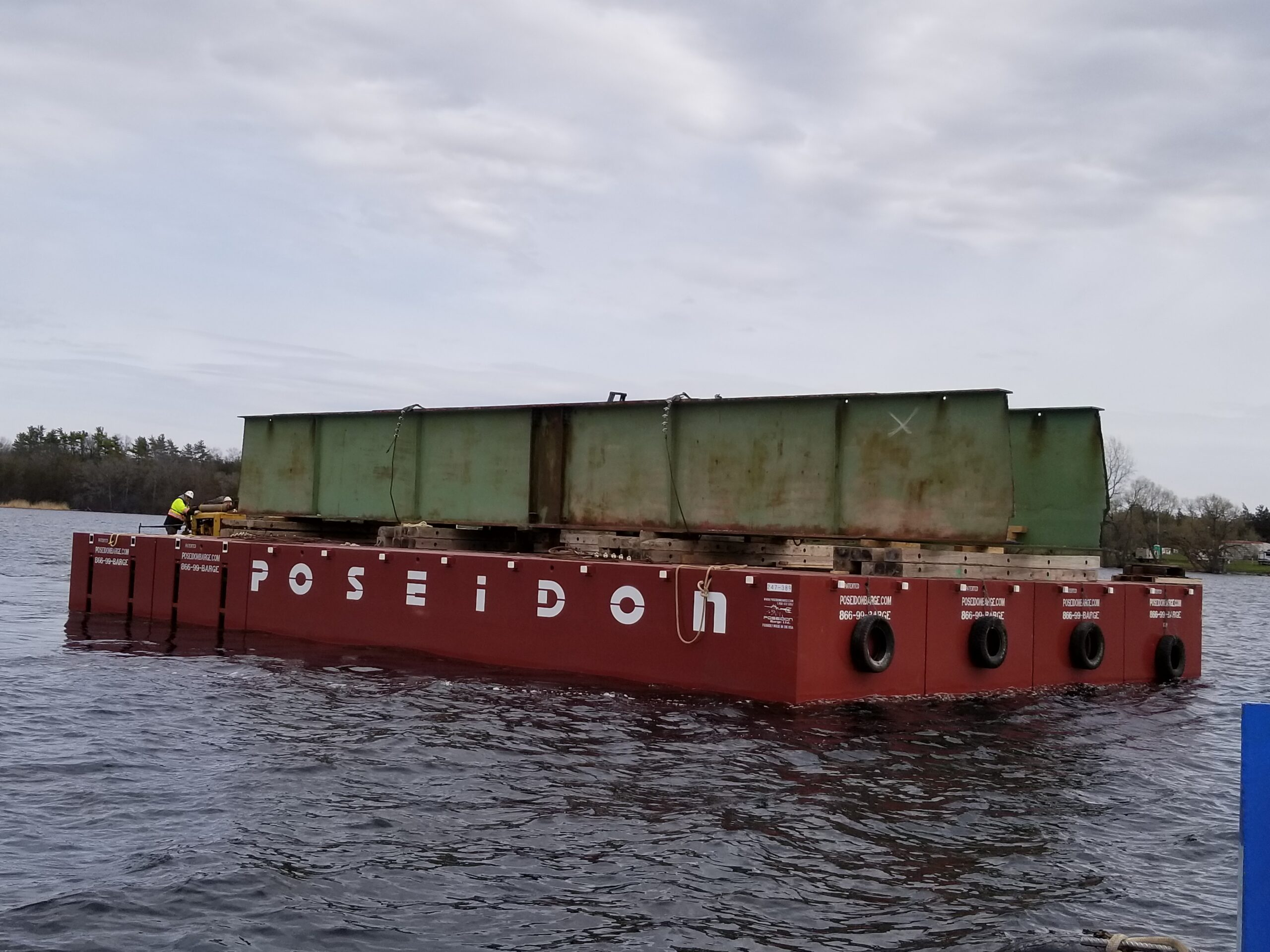 Removed girder section being moved by the barge to the shore