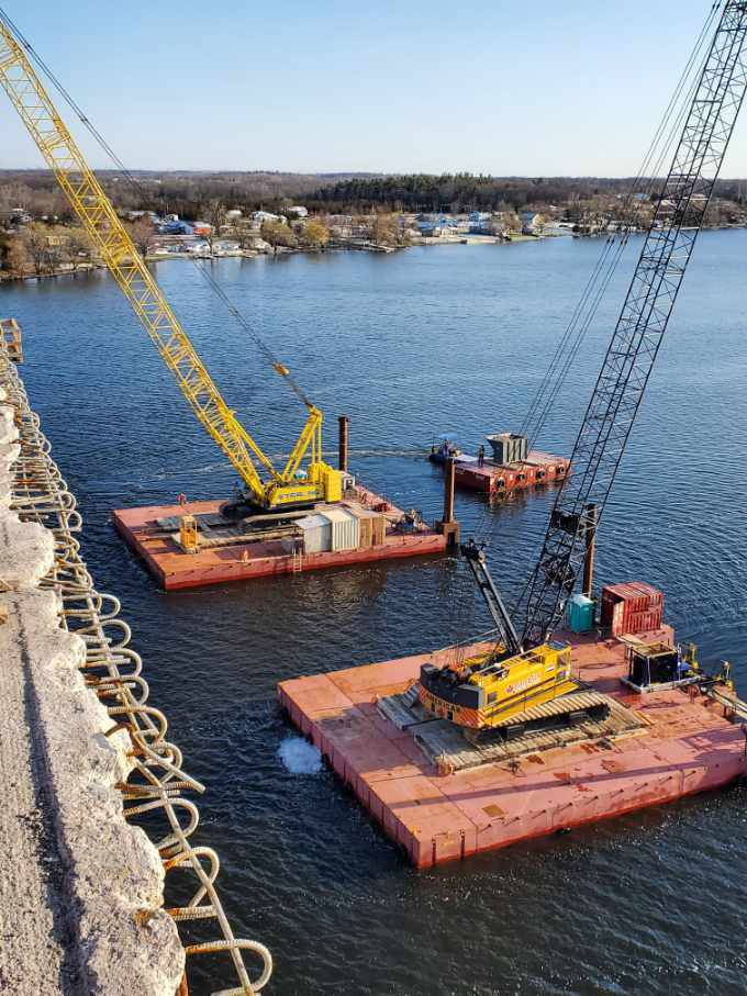 View from the bridge of the two cranes and barges / the boat removing a full containment bin from the barge