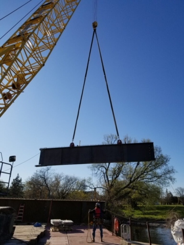 Girder piece being moved by the crane to the barge for assembly