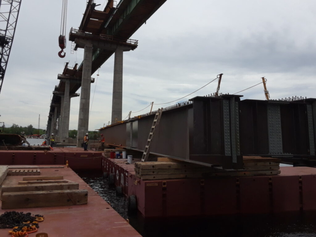 Barge with second approach girder being moved into place to be lifted