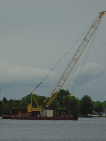 Barge with the final girder section moved out to the piers before placement
