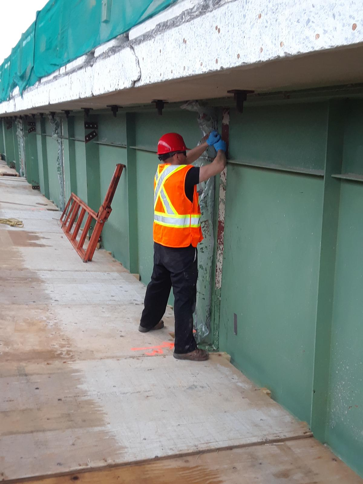 Stripping paint from the girder for temporary connection installation