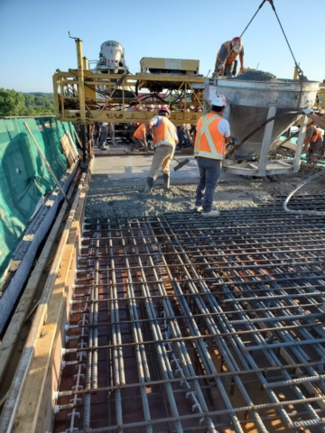 Concrete hopper containing concrete being lowered to the deck