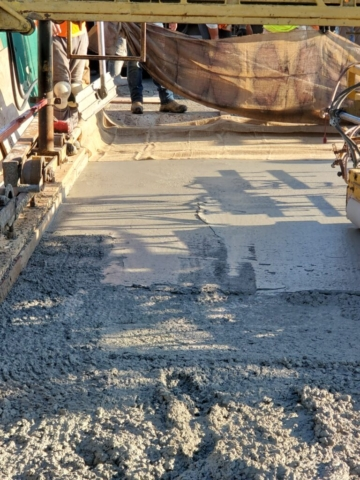 Wet burlap being placed on the fresh concrete