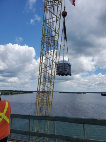 Container of water and burlap being lifted from the barge