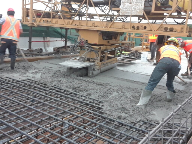 Newly placed concrete being vibrated and spread