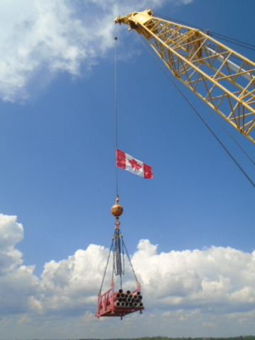 Crane lifting the pipes to the barge