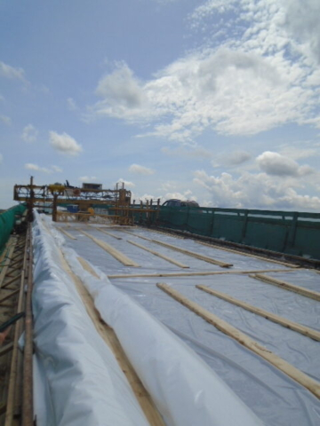 Plastic tarps and water hoses covering the newly placed concrete