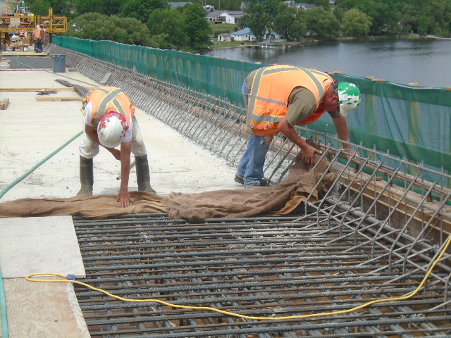 Placing wet burlap on the edge of the newly finished concrete section