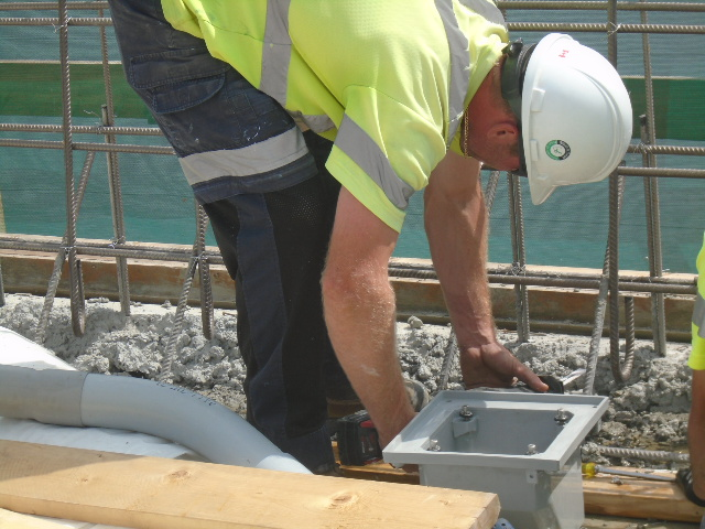 Installing conduit on the barrier wall rebar