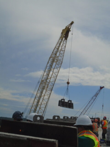 200 ton crane lifting barrier wall forms to the deck