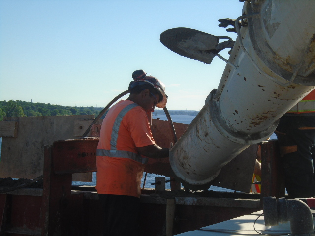 Vibrating the concrete as it is offloaded from the truck