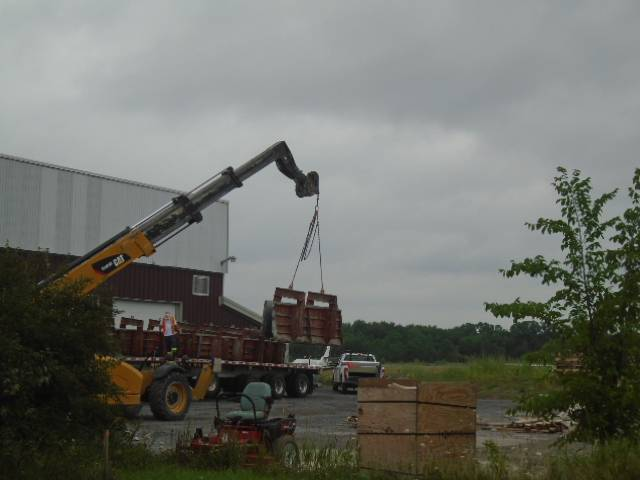 Barrier wall forms being offloaded for storage