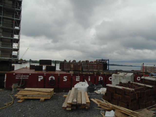 Barrier wall forms being brought to the dock on the barge