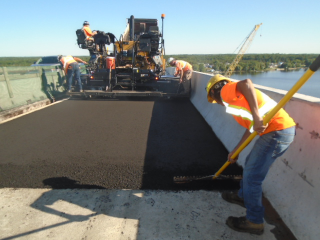 Spreading and evening the edge of the newly placed asphalt