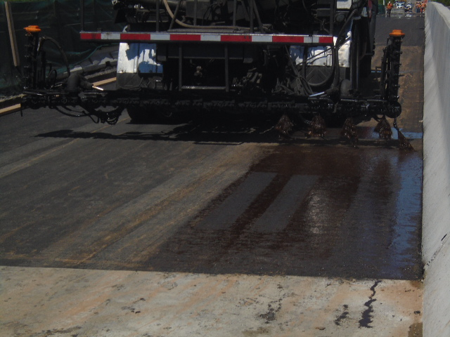 Tack coat truck spraying the first placement of asphalt