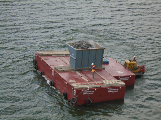 Full Containment bin being moved by the barge to the shore