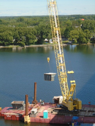 Lowering full containment bin to the barge