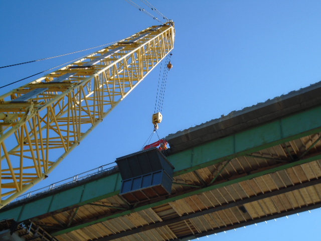 View from the barge of the containment bin being lifted by the crane