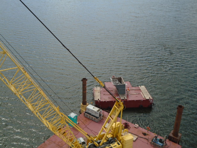 Full containment bin being moved to the shore for disposal