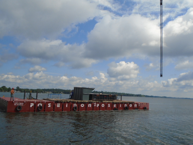 Containment bins being brought to shore by the barge