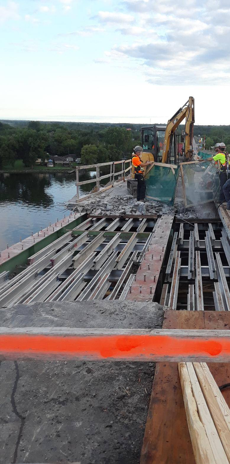 Hoe-ramming the concrete deck / containment screens / exposed girders