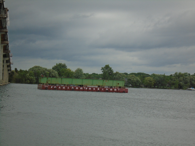 First girder section being removed to shore by barge